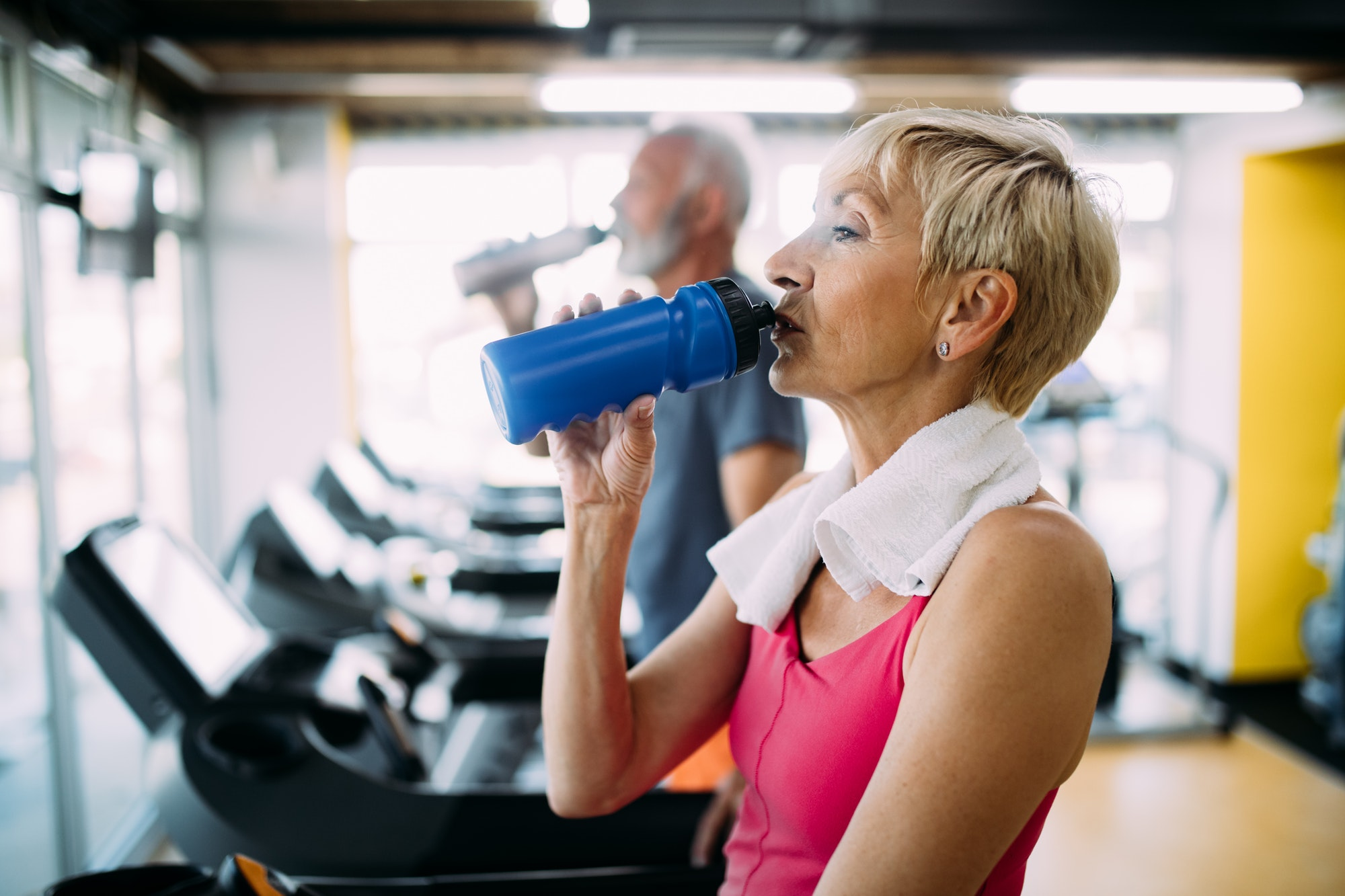 Senior woman drinking bottle of water on threadmill in gym